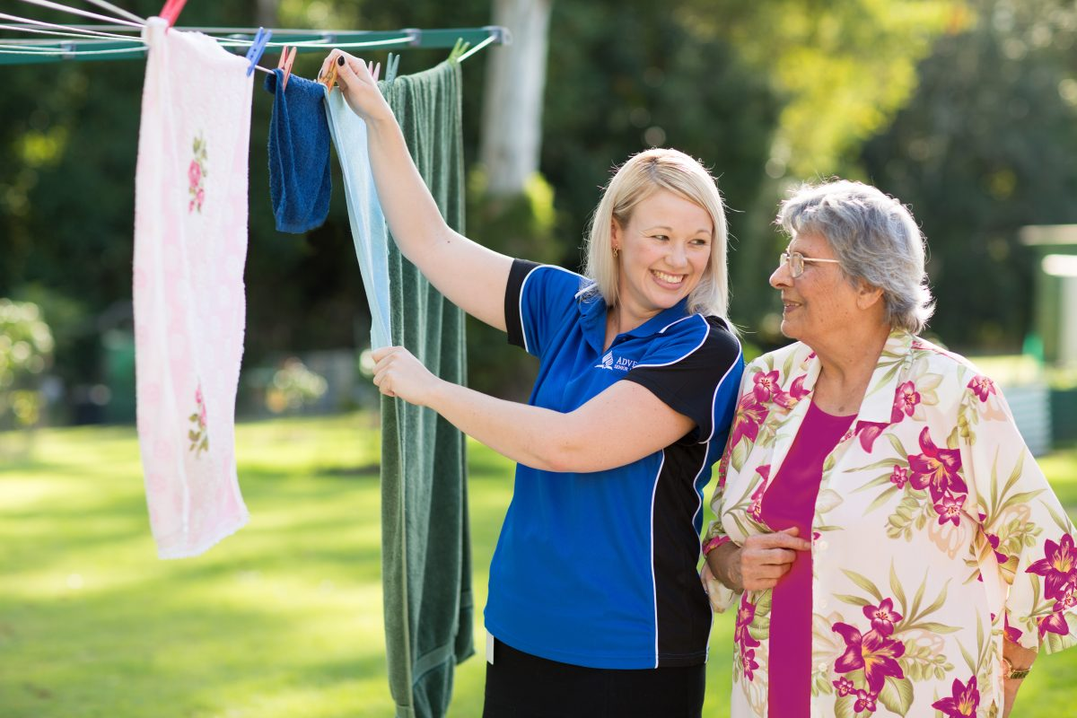 Carer helping Lady with putting washing on the wash line